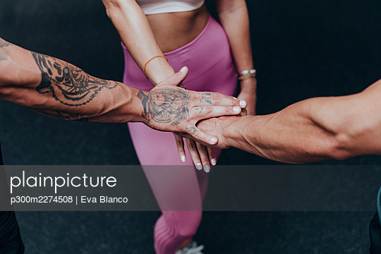 Sportswoman hand stacked with friends in gym - p300m2274508 by Eva Blanco