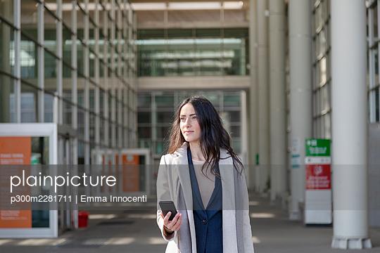 Elegant smart woman walking to work holding mobile phone; Florence, Italy - p300m2281711 von Emma Innocenti