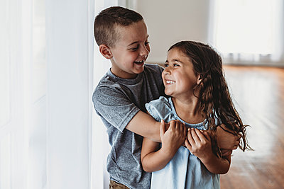 Brother and sister laughing at each other in natural-light studio - p1166m2130728 by Cavan Images