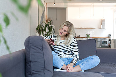 Young woman using smartphone on sofa - p1301m1582588 by Delia Baum