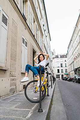 Playful young woman on bicycle at the roadside - p300m2023525 by VITTA GALLERY