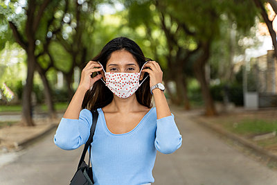 Beautiful female wearing protective face mask during COVID-19 - p300m2224936 by VITTA GALLERY