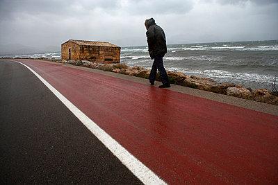 Man walking on coastline - p312m746782 by Peter Hoelstad