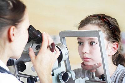 Optometrist examining girl's eyes - p429m872953 by Sigrid Gombert