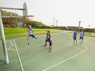 Basketball teams playing on court - p555m1415524 by Erik Isakson
