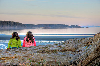 Young First Nation girls  sitting on a log, Vancouver Island, British Columbia - p6071799 by Robert Postma