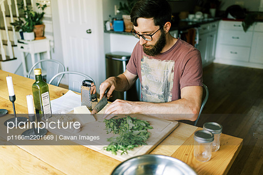 A young man chopping fresh homegrown basil for homemade pesto - p1166m2201669 by Cavan Images