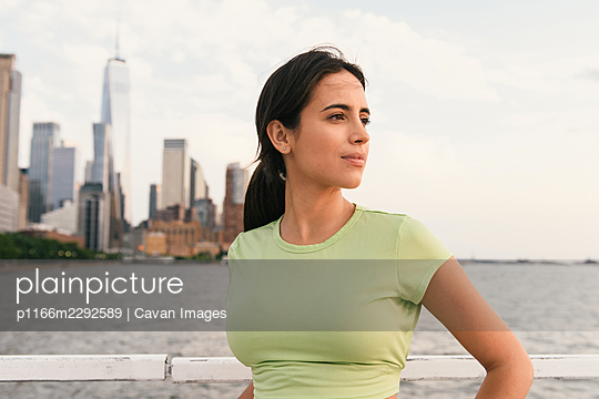 Horizontal view of jogger resting with south Manhattan in background - p1166m2292589 by Cavan Images