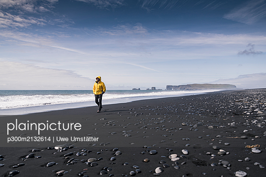 Mature man walking on a lava beach in Iceland - p300m2132614 by Uwe Umstätter