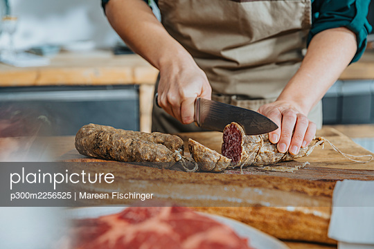 Female chef cutting salami on cutting board while standing in kitchen - p300m2256525 by Mareen Fischinger