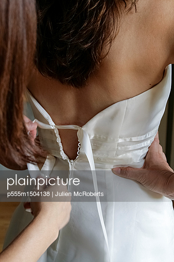 Woman lacing back of wedding dress - p555m1504138 by Julien McRoberts