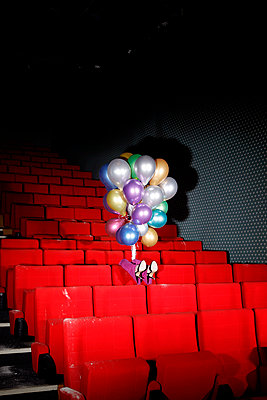 Woman with colourful balloons in vintage cinema hall - p1105m2254508 by Virginie Plauchut