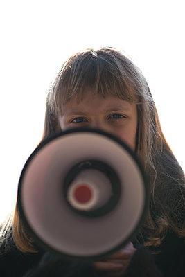 Teenage girl holding megaphone - p1631m2208652 by Raphaël Lorand