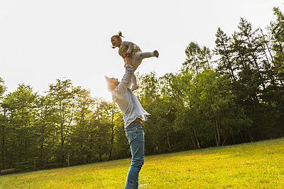 Father lifting up daughter on meadow - p300m1028649f by Uwe Umstätter