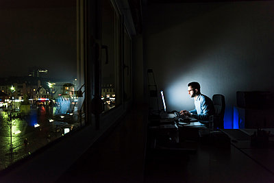 Businessman working on computer in dark office - p300m1581310 von Uwe Umstätter