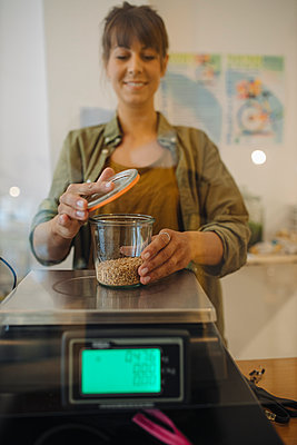Female owner weighing grain jar on weight scale in cafe - p300m2226173 by Gustafsson