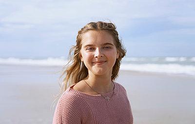 Portrait of teenage girl standing on beach - p300m2273691 by Arman Zhenikeyev