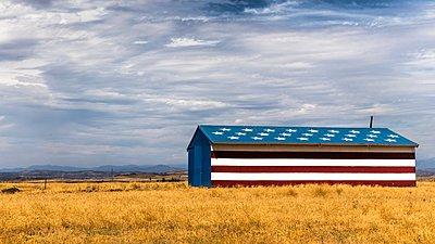 Barn in field painted with stars and stripes, California, USA - p429m1118496f by Aziz Ary Neto