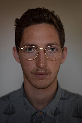 Portrait of young man wearing eyeglasses - p552m1589969 by Leander Hopf