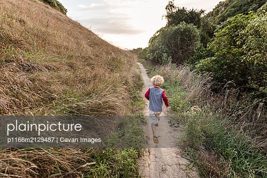 Toddler boy running on a hillside trail - p1166m2129487 by Cavan Images