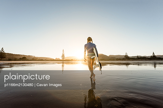 Young female carrying surfboard at beach - p1166m2130480 by Cavan Images