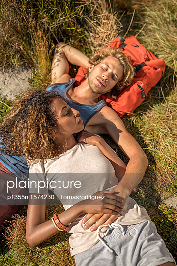 Junges Paar macht eine Pause beim Wandern - p1355m1574230 von Tomasrodriguez