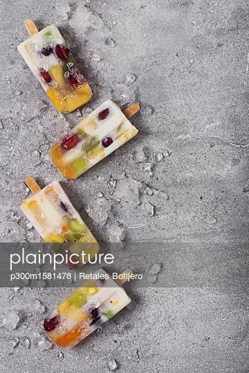 Homemade fruits and yogurt ice lollies on marble - p300m1581478 von Retales Botijero