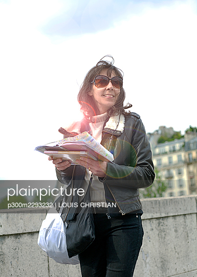 Smiling woman holding guidebook and map while standing by retaining wall - p300m2293232 by LOUIS CHRISTIAN