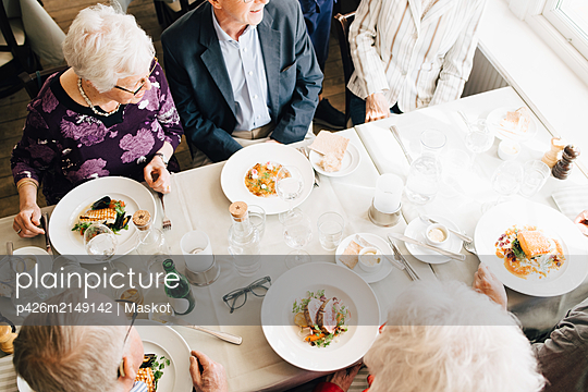 High angle view of Senior friends with food in restaurant - p426m2149142 by Maskot