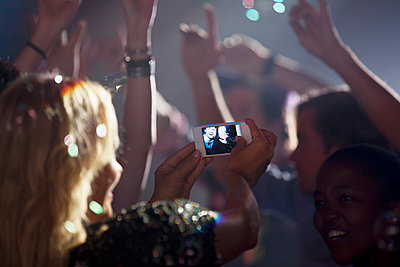 Woman with camera phone photographing friends on dance floor of nightclub - p1023m930660f by Sam Edwards