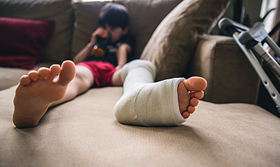 Boy with fractured leg sitting on sofa at home - p1166m2011866 by Cavan Images