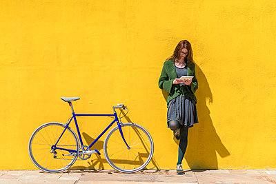 Businesswoman using tablet computer while standing on sidewalk by bicycle against yellow wall during sunny day - p1166m2060572 by Cavan Social