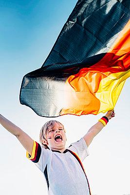 Boy, enthusiastic for soccer world championship, waving German flag - p300m2005473 von Jana Mänz