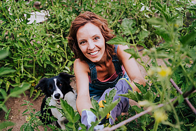 Smiling woman with border collie working in vegetable garden - p300m2202536 by Eva Blanco