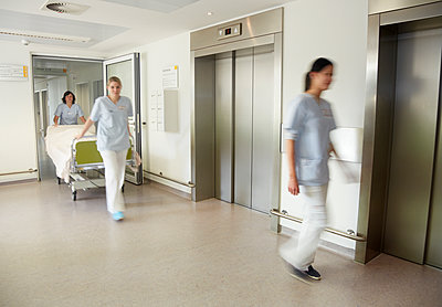 Germany, Freiburg, Nurses moving hospital bed - p300m2213694 by Heinz Linke