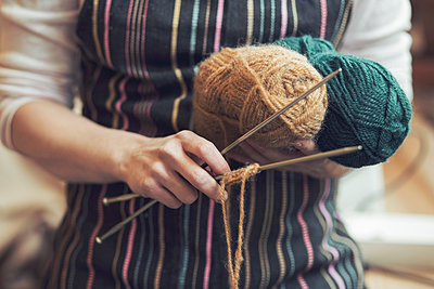 Midsection of woman holding knitting tools at home - p426m958693f by Maskot