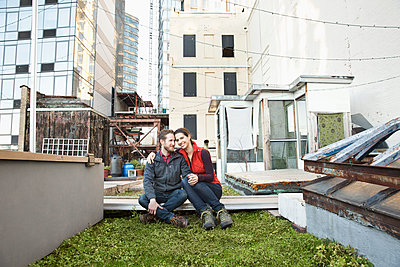 Couple smiling in urban rooftop garden - p555m1304759 by Jasper Cole
