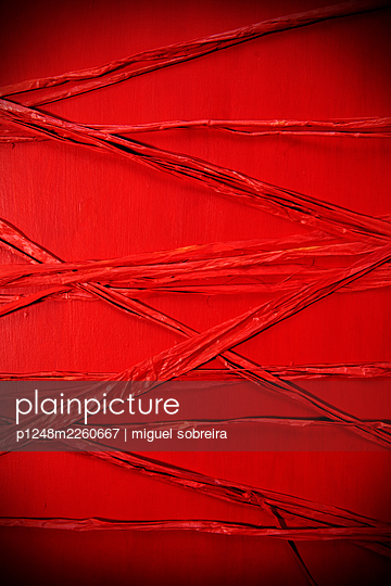 Bast string against red background - p1248m2260667 by miguel sobreira
