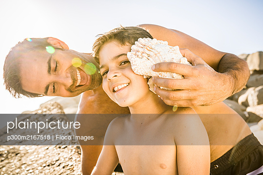 Father and son having fun on the beach and listening to the ocean in a shell - p300m2167518 by Floco Images
