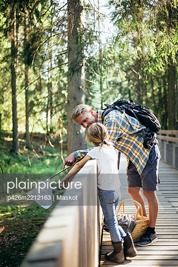 Father with backpack talking to daughter on footbridge in forest - p426m2212163 by Maskot