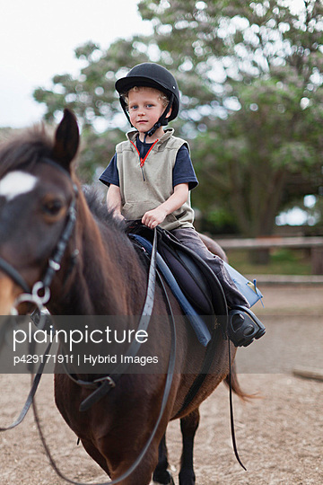Boy riding horse in yard - p42917191f by Hybrid Images