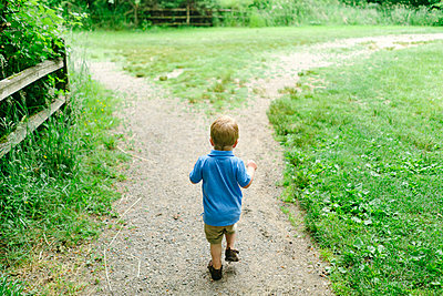 Rear view of a young boy walking down a path - p1166m2093840 by Cavan Images