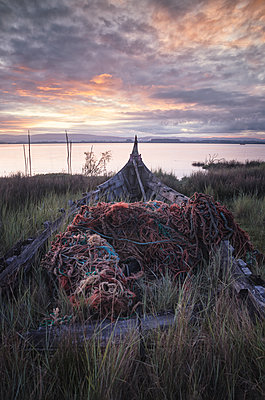 old abandoned boat covered in fishing nets - p1166m2152247 by Cavan Images