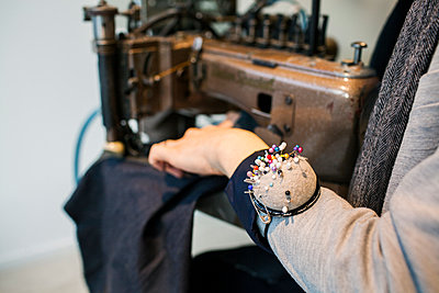 Midsection of male fashion designer wearing pin cushion while using sewing machine in jeans factory - p1185m994336f by Astrakan
