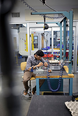 Focused male engineer assembling circuit board in research lab - p1192m2105186 by Hero Images