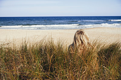 Serene woman sitting in the grass at Pacific ocean - p1577m2150348 by zhenikeyev
