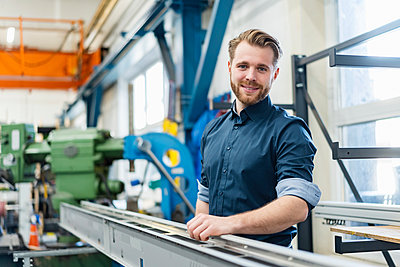 Portrait of a smiling young man in a factory - p300m2188353 by Daniel Ingold