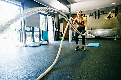 Mixed Race woman working out with heavy ropes in gymnasium - p555m1304149 by Peathegee Inc