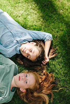 Zwei Mädchen entspannen im Gras - p586m1109372 von Kniel Synnatzschke