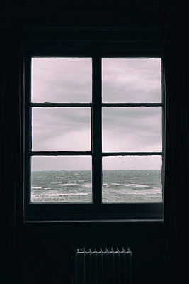 Rain spattered window with view of rough sea  - p597m2077107 by Tim Robinson